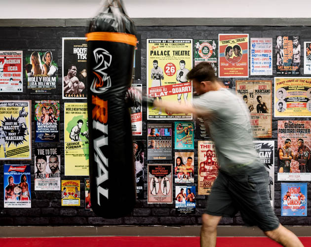 Member boxing with boxing posters in the background