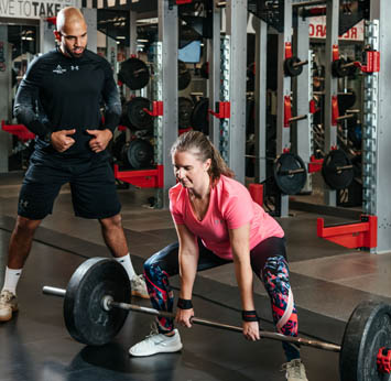 Trainer working with female client in the Strength Gym
