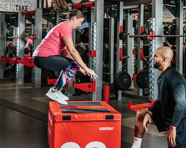 Member doing box jumps with trainer nearby in Strength Gym
